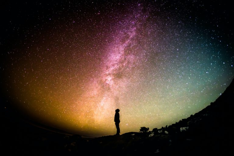 person staring up into a night sky full of color and stars