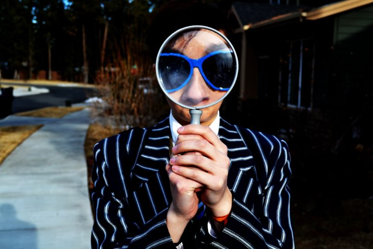 man in sunglasses looking through a magnifying glass